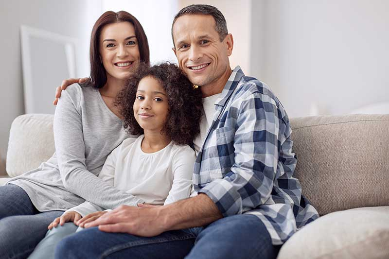 Pretty happy curly-haired girl smiling and sitting on the couch with her parents and they hugging her.