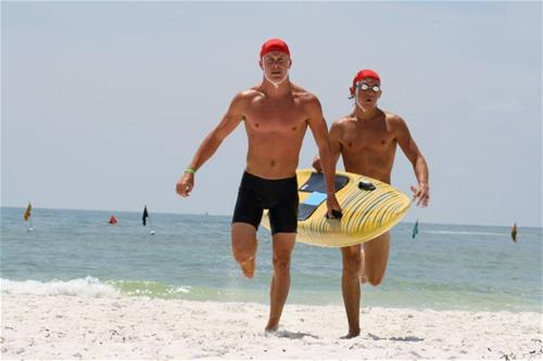 2 lifeguards running in from ocean