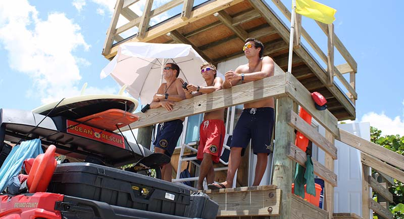 3 lifeguards looking over the beach from a lifeguard tower.