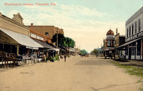 Washington Aveue in Titusville, Florida from late 1800's. A couple horsedrawn carriages and an automobile appear on an empty dirt road.