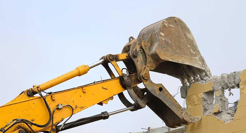 Backhoe pulling a wall.