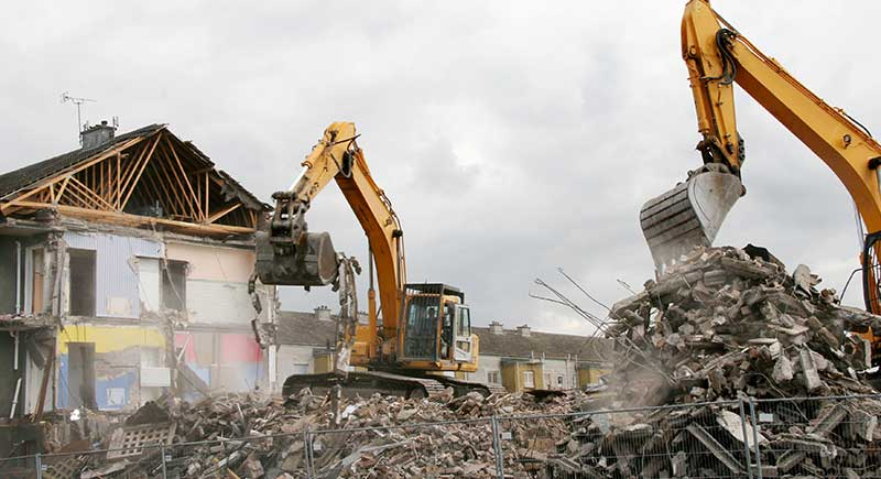 Backhoes demolishing a house.