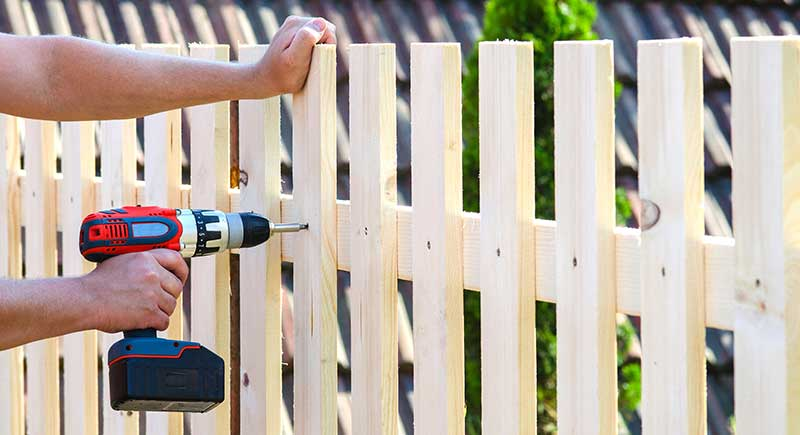 Man building a wooden fence with a drill and screw. Close up of his drill.
