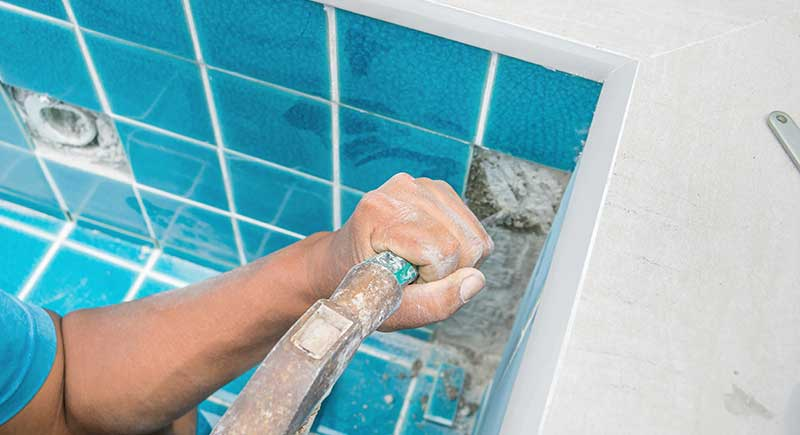 Tiled pool. A mans hand while using spacer for installing tiles.