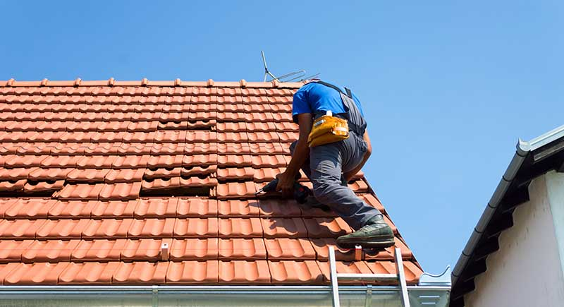 Worker repairing tiles on a roof.