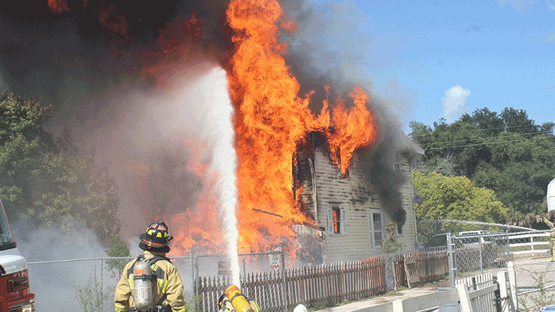 Firefighters spraying water on a buring house with a firehose.