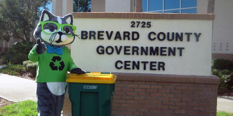 RC the Recycling Cat standing in front of the Brevard County Government Center building with a recycling trash bin.
