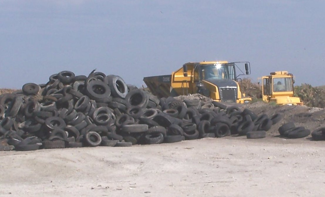 Dump truck and backhoe parked next to a large pile of used tires.