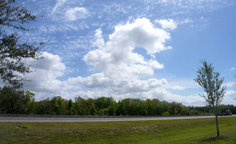 Traveling south on Interstate 95 near Mims, Florida, on a sunny day, accompanied by beautiful white cumulus clouds.