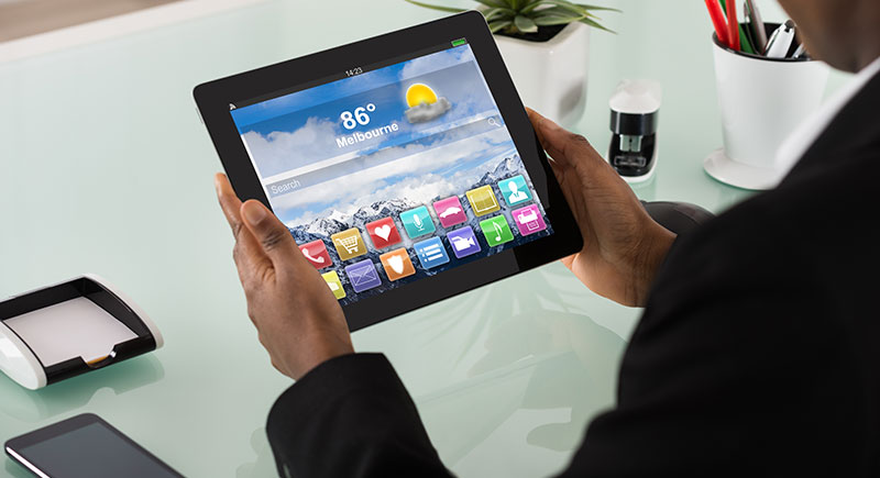 Person looking at weather forecast on a tablet.