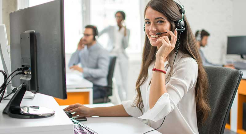 Young friendly operator woman agent with headsets working in a call center.