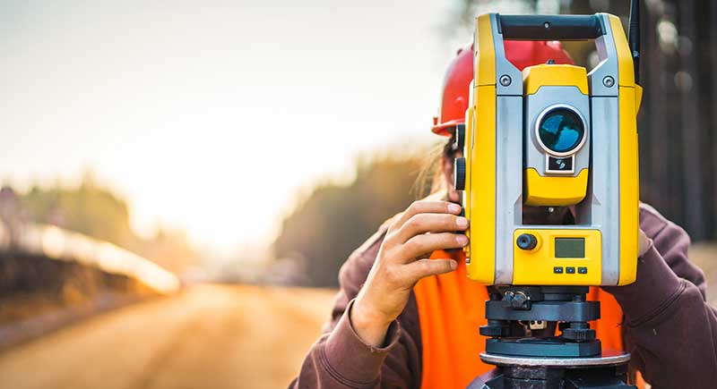 Surveyor engineer with equipment on the construction site of the road with construction machinery background.