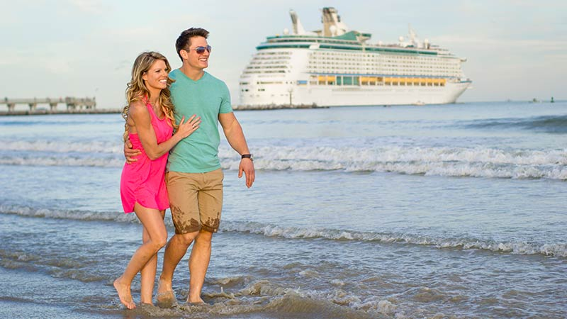 Young couple walking on the beach with a cruise ship in the background.